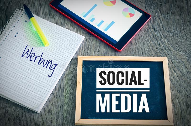 Plat avec le media social d'inscription et en allemand Werbung dans la publicité anglaise avec un comprimé et un blockto pour sym images libres de droits