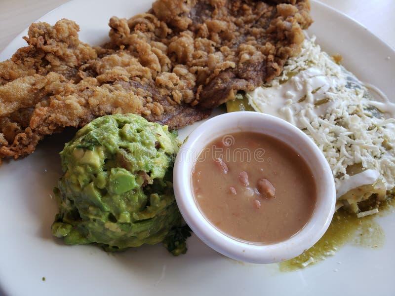 plat avec le milanesa de boeuf, chilaquiles en sauce verte, guacamole et haricots photographie stock libre de droits