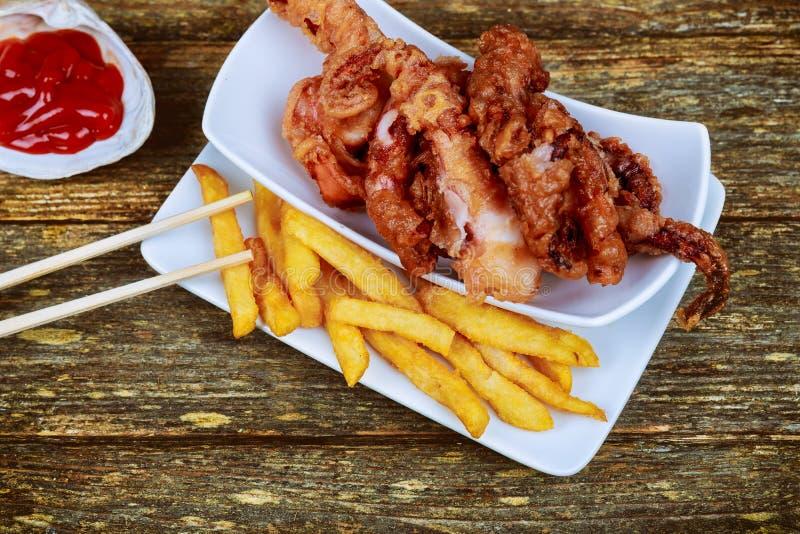 Plat avec le poulpe cuit au four avec les pommes de terre et la sauce frites photo stock