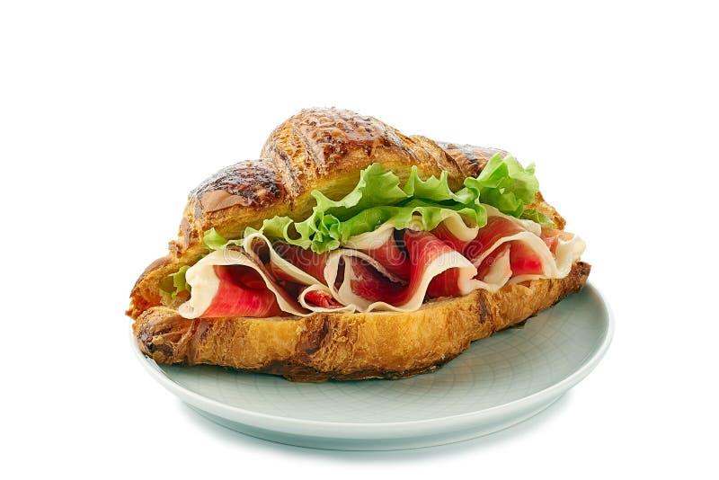 Plat avec le sandwich à croissant avec le jamon du jambon et de la laitue sur le blanc photographie stock libre de droits