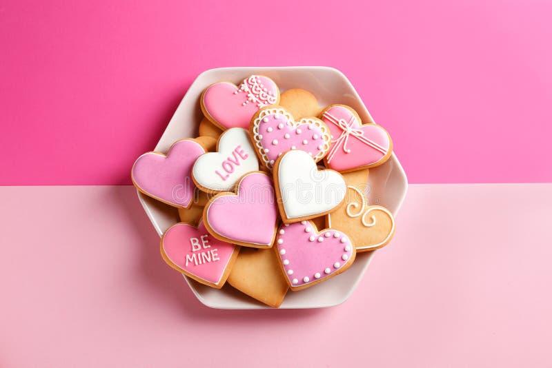 Plat avec les biscuits en forme de coeur décorés sur le fond de couleur, vue supérieure Jour du `s de Valentine photographie stock