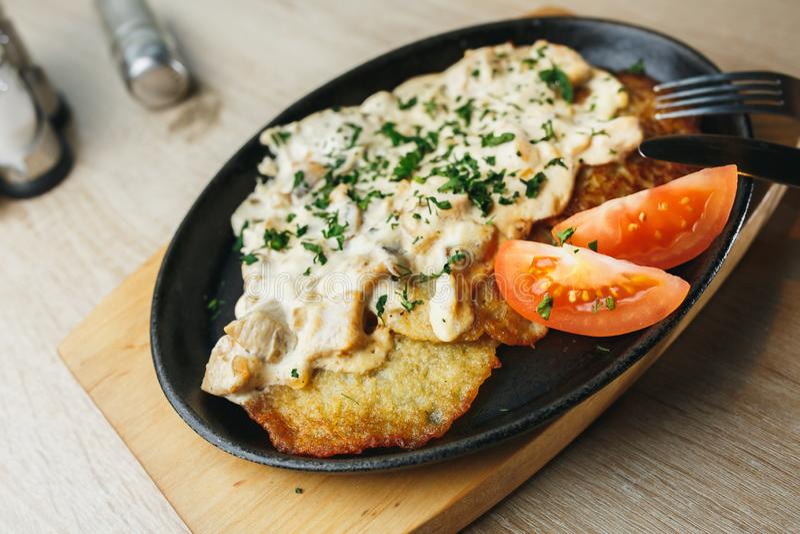 Plat avec les crêpes de pomme de terre savoureuses avec les tomates et la sauce au jus sur la table en bois image libre de droits