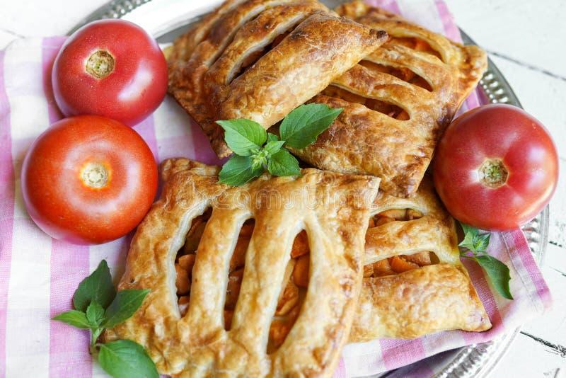 Plat avec les gâteaux faits maison et la pâte feuilletée avec des tomates sur la table photos libres de droits