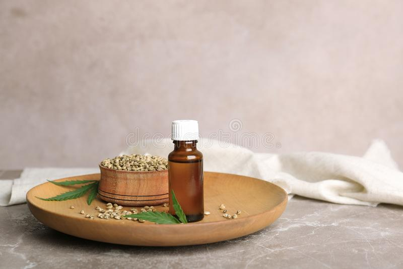 Plat avec les graines de chanvre et la bouteille de l'extrait image stock