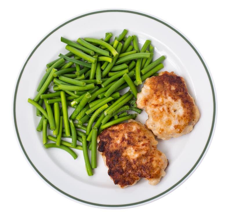 Plat avec les haricots verts et la viande sur le fond blanc, vue supérieure photographie stock