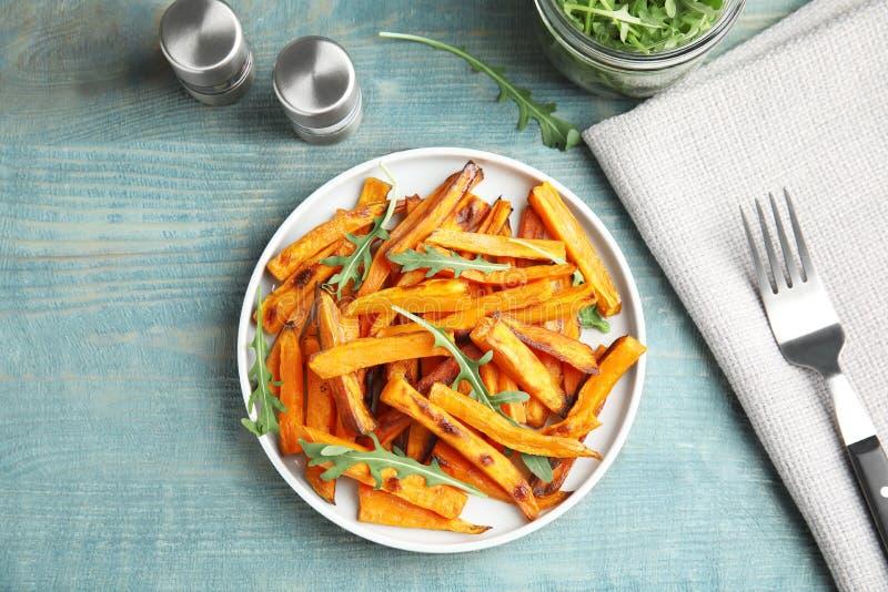 Plat avec les tranches cuites au four de patate douce et arugula servi sur la table en bois image libre de droits