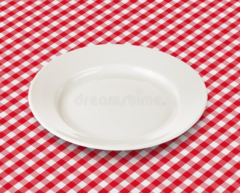 Plat blanc au-dessus de nappe rouge de pique-nique image stock