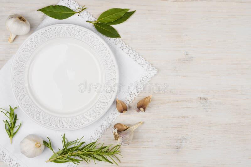 Plat blanc avec l'ail, la feuille de laurier et le romarin sur le bois photos libres de droits