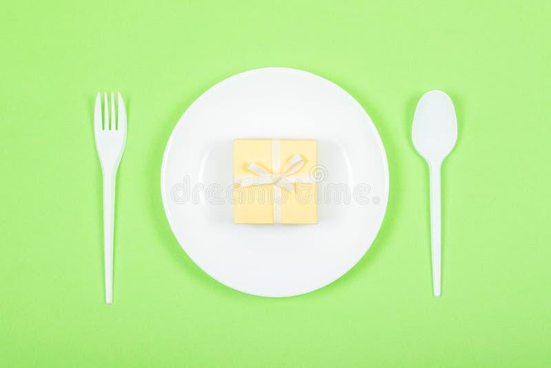 Plat blanc avec le boîte-cadeau jaune, cuillère, fourchette sur le fond vert De fête, anniversaire, fond minimal en pastel de cad images libres de droits