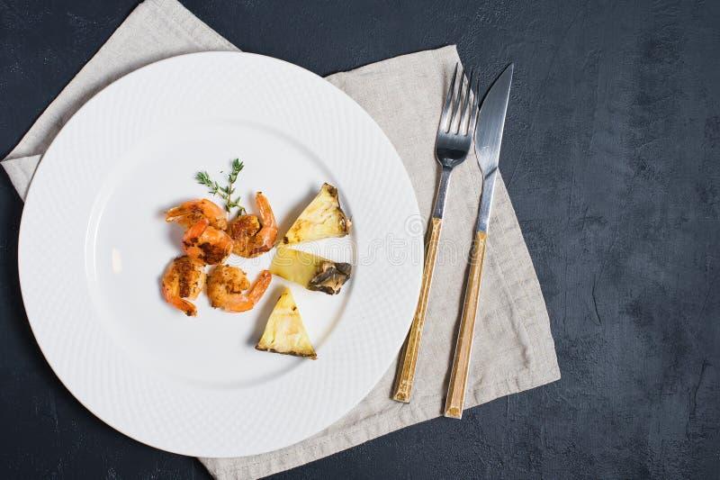 Plat blanc avec les crevettes roses de roi et les tranches frites d'ananas images libres de droits