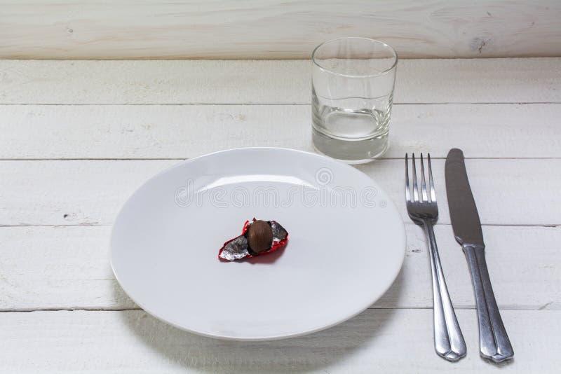 Plat blanc avec un petit oeuf de pâques de chocolat dans l'aluminium rouge ouvert, photographie stock