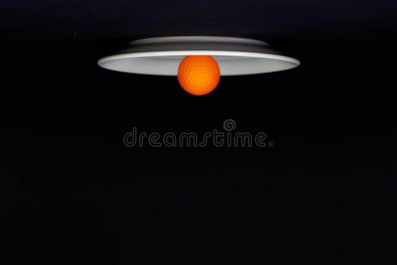 Plat blanc et boule de golf orange sur la table noire photo stock