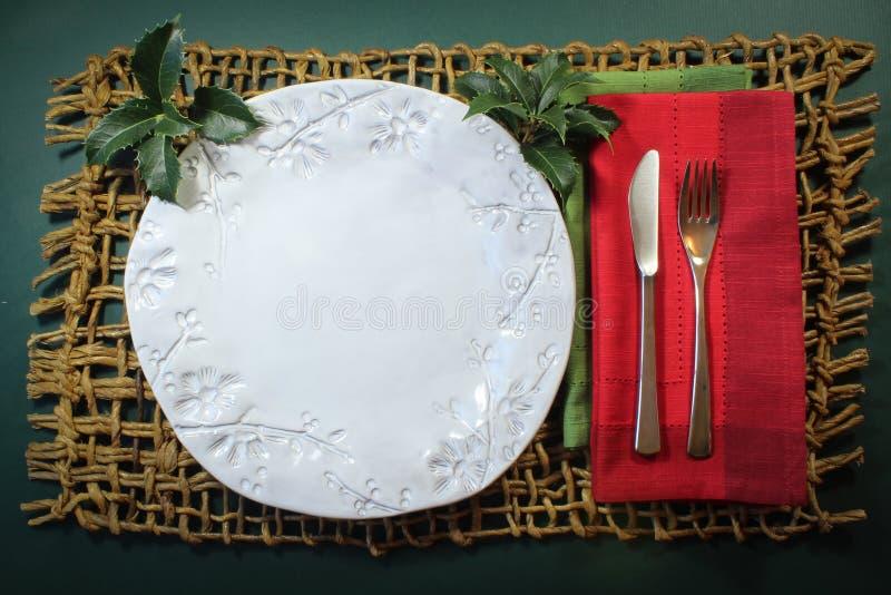 Plat blanc fait main avec les serviettes rouges et vertes avec le houx sur un fond occasionnel tissé rustique de Noël de tapis image libre de droits