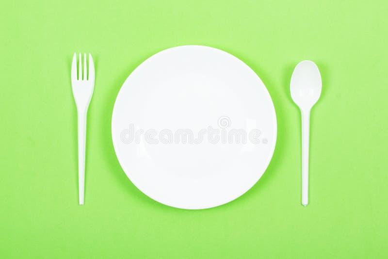 Plat blanc rond vide avec la cuillère, fourchette sur le fond vert Cuisine, faisant cuire, cuisine, maquette de restaurant de men photos libres de droits