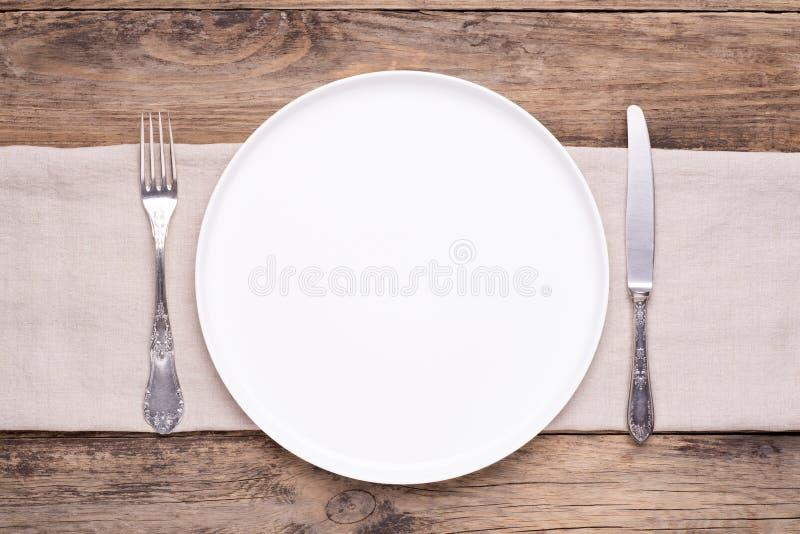 Plat blanc vide avec la serviette et couverts argentés sur la vieille table en bois photos libres de droits