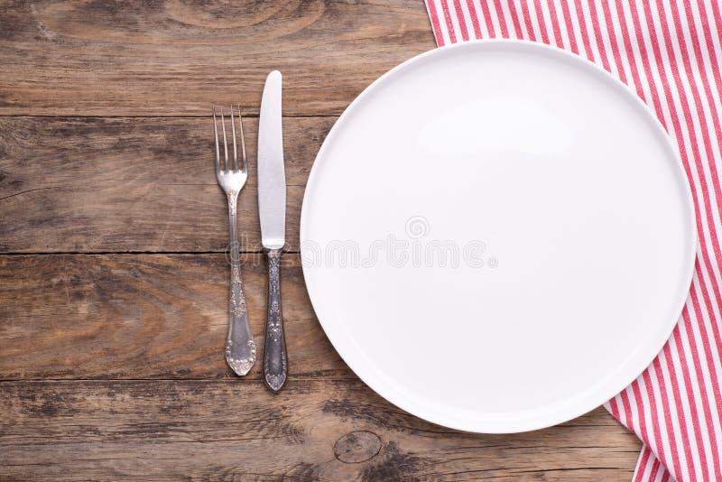 Plat blanc vide avec la serviette et couverts argent?s sur la vieille table en bois image stock
