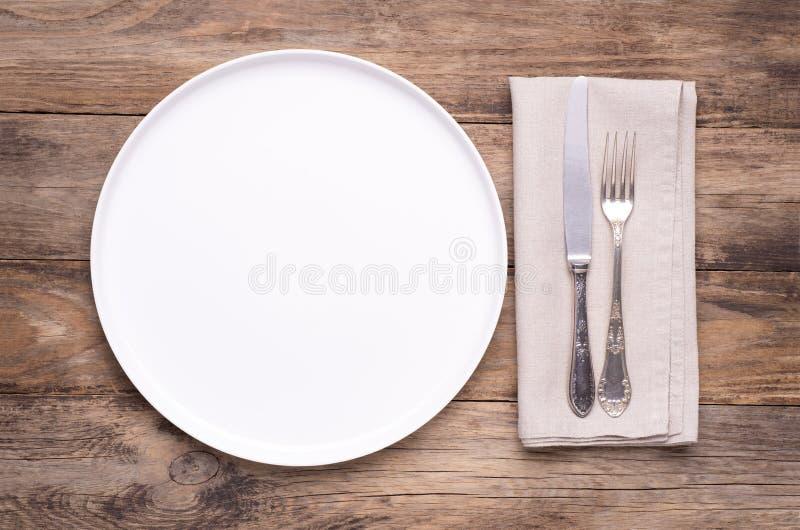 Plat blanc vide avec la serviette et couverts argent?s sur la vieille table en bois image libre de droits