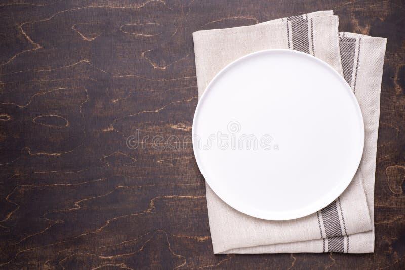 Plat blanc vide avec la serviette sur la table en bois foncée photos libres de droits