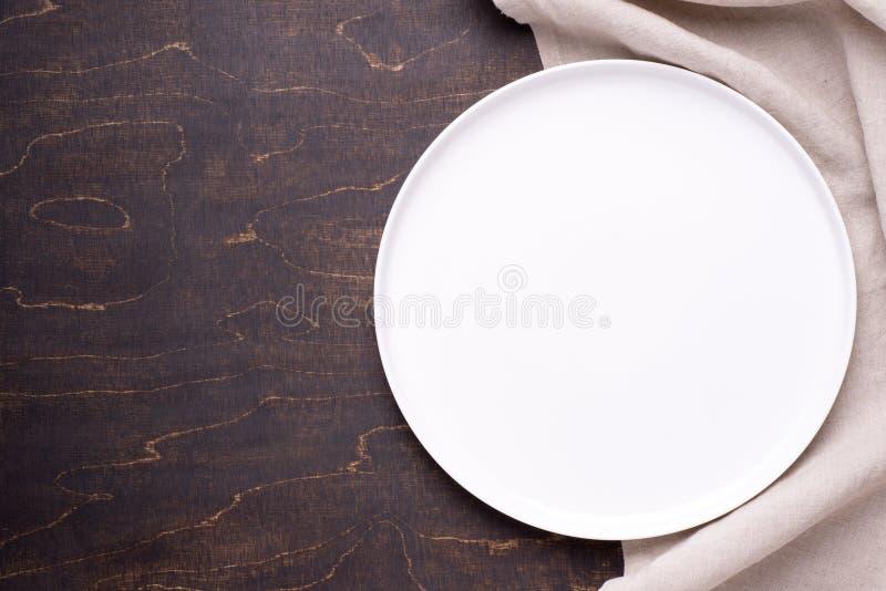 Plat blanc vide avec la serviette sur la table en bois fonc?e photo libre de droits
