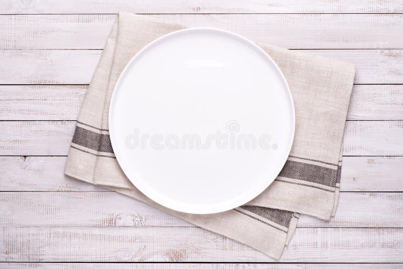 Plat blanc vide avec la serviette sur la vieille table en bois image libre de droits
