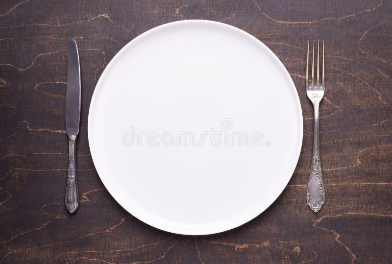 Plat blanc vide et couverts argentés sur la table en bois foncée photos stock