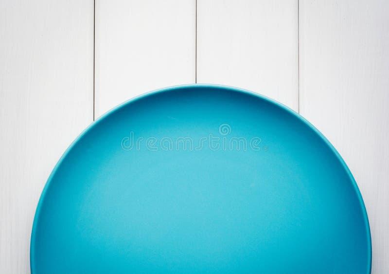 Plat bleu vide sur le fond en bois blanc Vue supérieure avec l'espace de copie photographie stock libre de droits