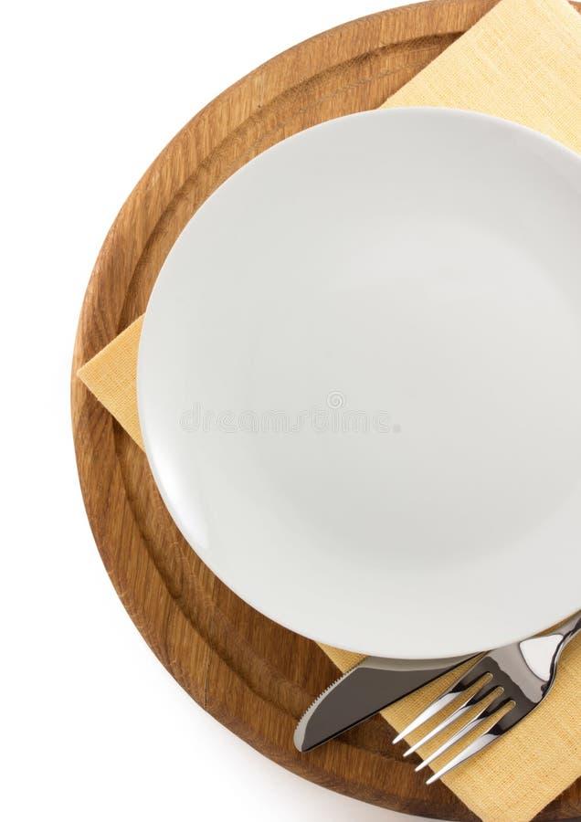 Plat, couteau et fourchette à la planche à découper photographie stock