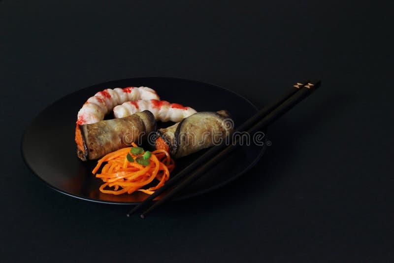 Plat culinaire asiatique des carottes marinées, cous de crevette et rouleaux d'aubergines frites bourrées des carottes sur le pla photo libre de droits