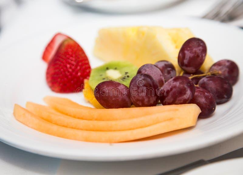 Plat découpé en tranches de fruit avec des raisins photographie stock
