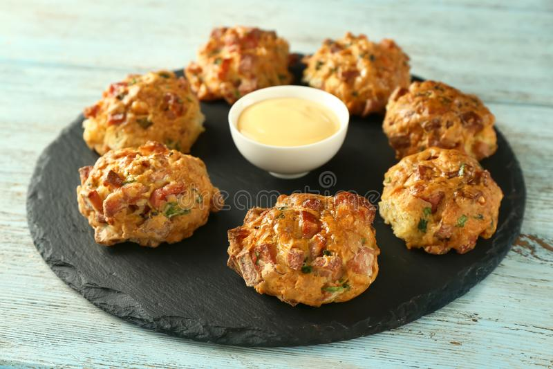 Plat d'ardoise avec les boules savoureuses de saucisse et sauce au fromage sur la table en bois photographie stock