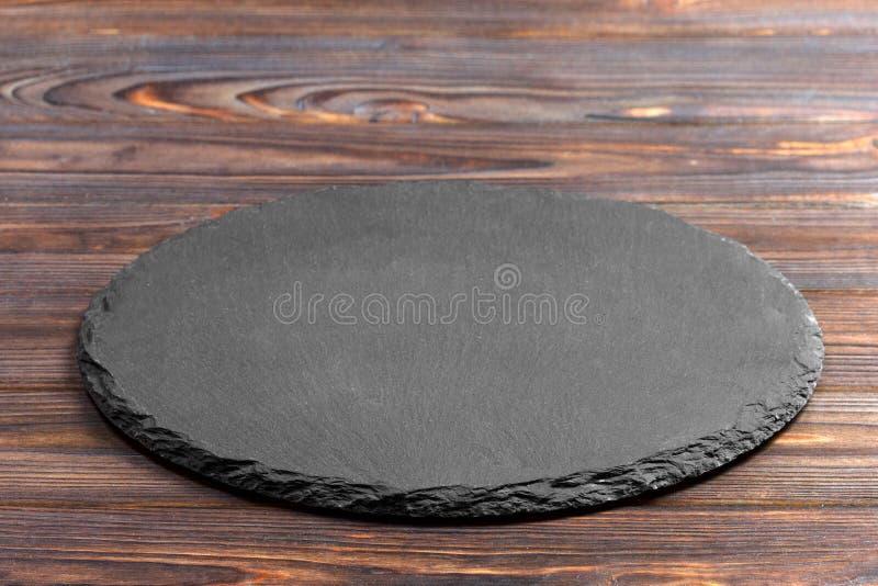 Plat d'ardoise sur la table Pierre noire d'ardoise sur le fond en bois Copiez l'espace image stock
