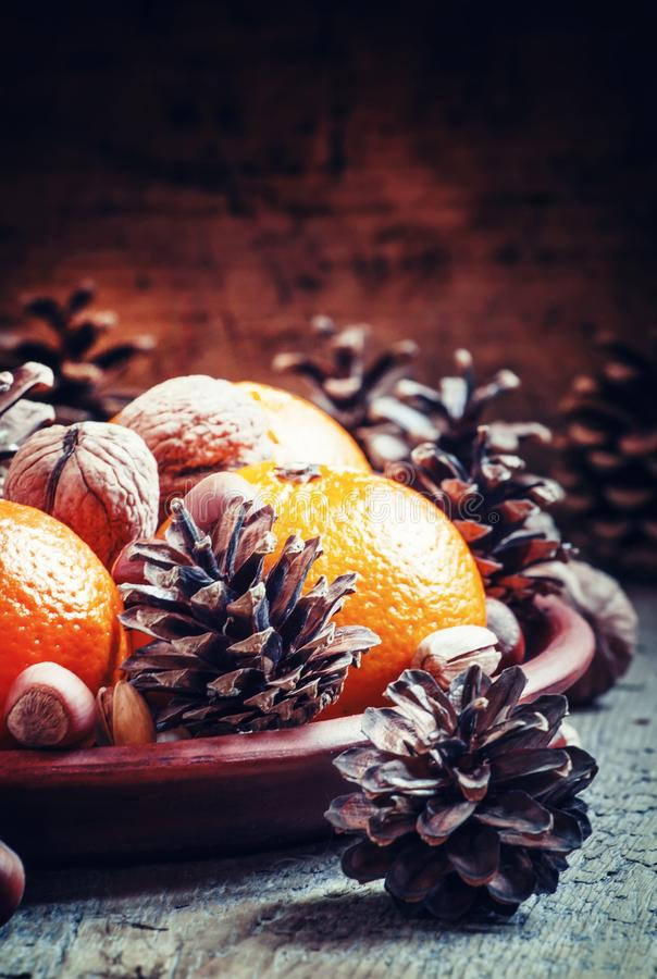 Plat d'argile avec les mandarines oranges, cônes de sapin, noix, noisettes photos libres de droits