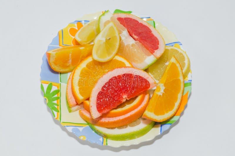 Plat d'orange coupée en tranches, de citron, de pamplemousse rose et de bonbon image libre de droits