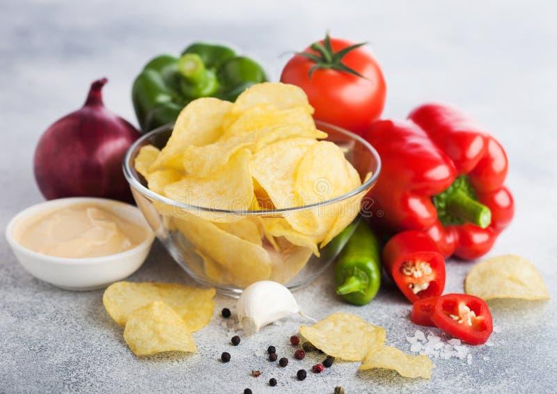 Plat de bol en verre avec des frites de pommes chips avec la saveur d'oignon sur le fond clair de table Poivre de piments rouge e photo libre de droits