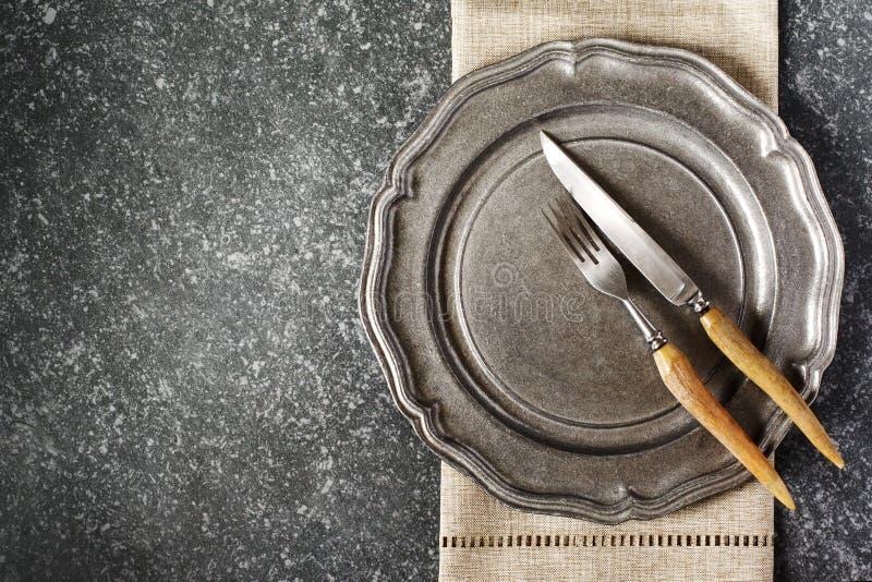 Plat de cru et fourchette et couteau vides avec la serviette sur le fond en pierre gris-foncé images libres de droits