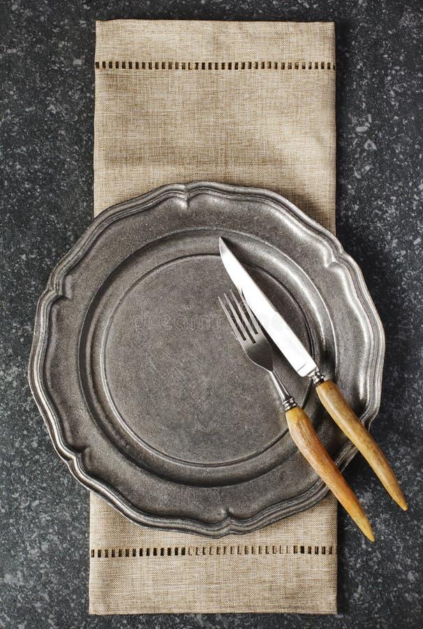Plat de cru et fourchette et couteau vides avec la serviette sur le fond en pierre gris-foncé image stock