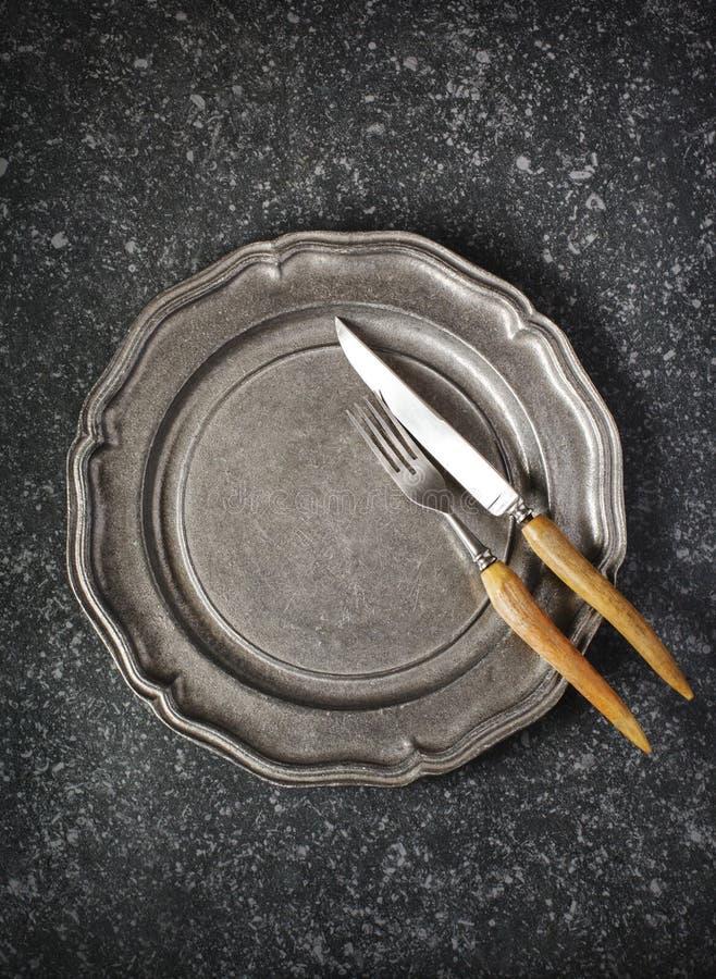 Plat de cru et fourchette et couteau vides sur le fond en pierre gris-foncé photo libre de droits