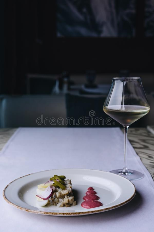 Plat de délicatesse de restaurant sur une nappe pourpre avec le verre de vin blanc photo stock