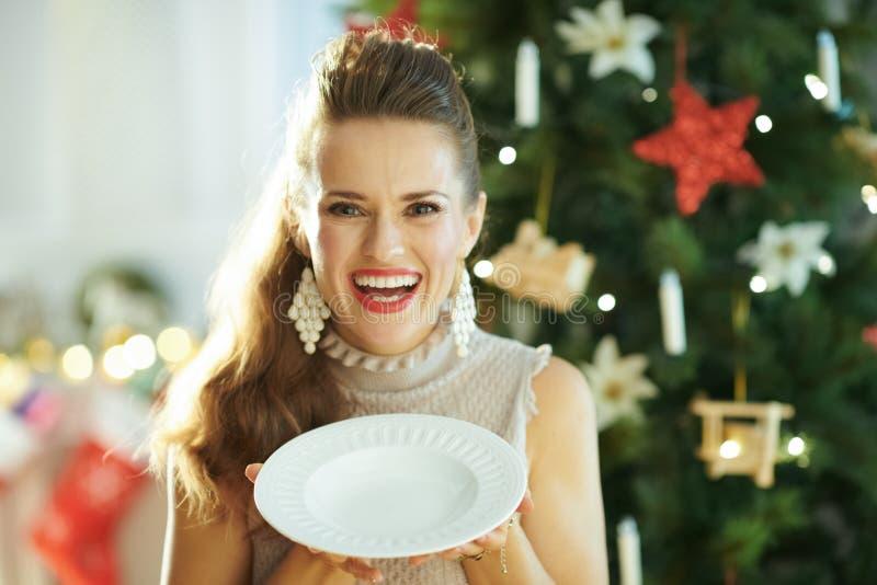 Plat de dîner blanc servant de sourire de participation à la mode de femme au foyer photos stock