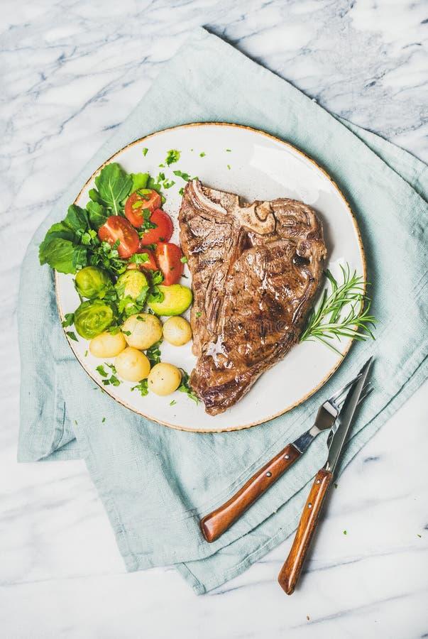 Plat de dîner grillé de viande avec le bifteck à l'os cuit de boeuf photographie stock libre de droits