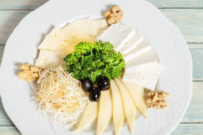 Plat de différents genres de fromage avec les olives et le persil images libres de droits