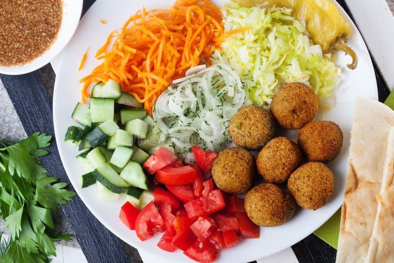 Plat de Falafel sur le dessus à garnir, carotte, chou, oignon, concombres, tomates, toujours la vie, plat images libres de droits