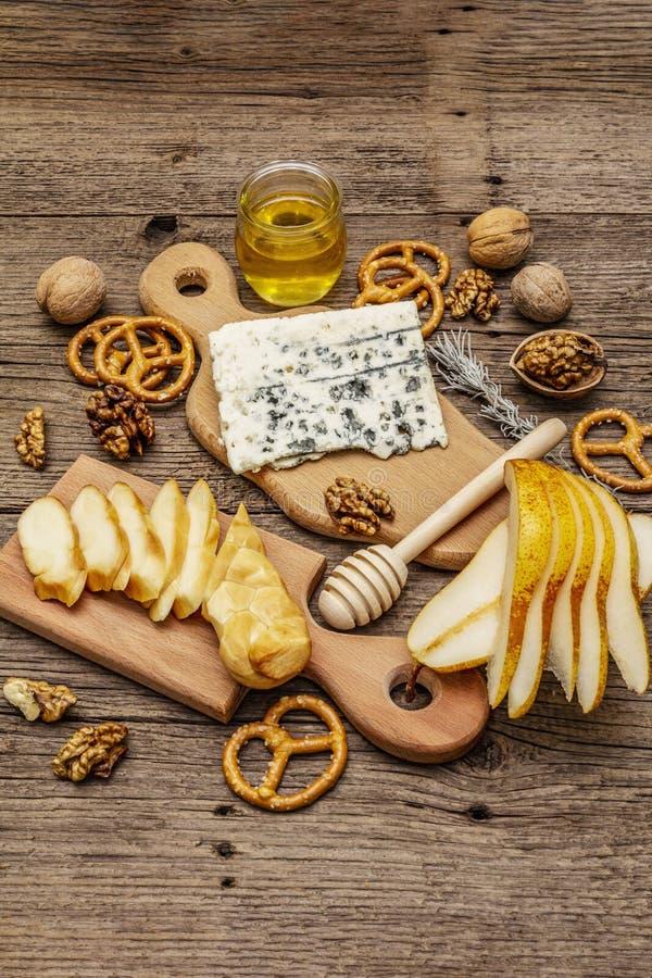 Plat de fromage antipasti avec fromage fumé et bleu, craquelins, miel, noix et poire mûre Une recette de collation traditionnelle images libres de droits