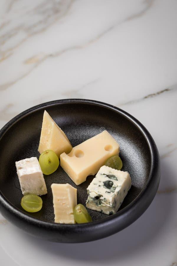 Plat de fromage avec la sélection Edamer, le parmesan, la chèvre, le bleu et le fromage fondu, le pair et les raisins sur le plat image libre de droits