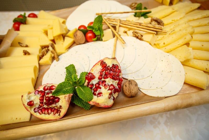 Plat de fromage avec la variété d'apéritifs sur la table photographie stock libre de droits