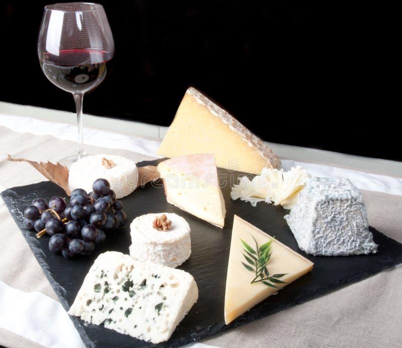 Plat de fromage avec le vin rouge, la vigne et le miel sur le fond noir photographie stock