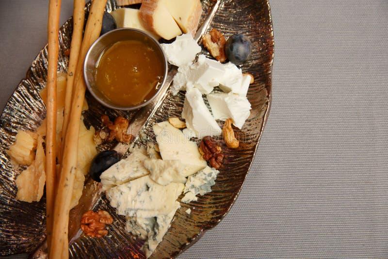 Plat de fromage : Emmental, fromage de camembert, fromage bleu, batons de pain, noix, noisettes, miel L'espace pour le texte photo libre de droits