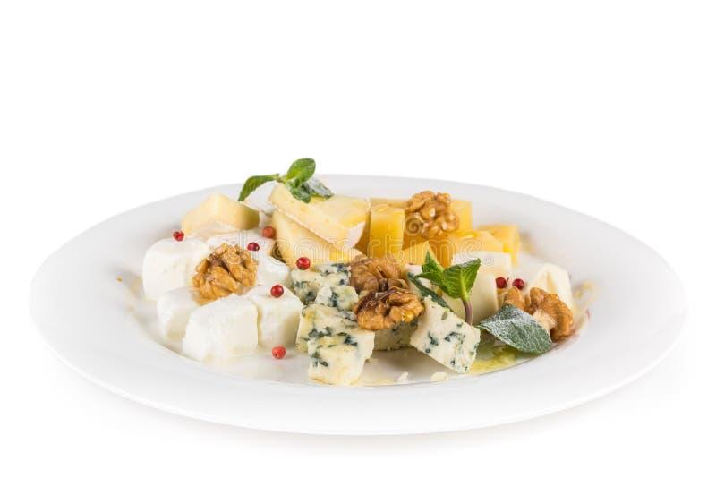 Plat de fromage : Parmesan, cheddar, Gouda, mozzarella et autre avec des noix, des canneberges et la menthe d'un plat D'isolement images stock