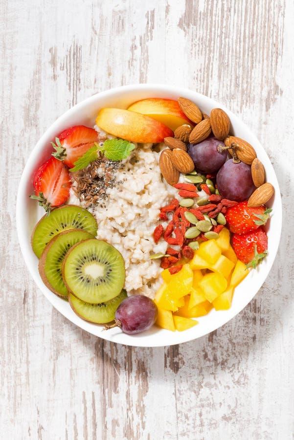 Plat de gruau de farine d'avoine avec le fruit frais et de superfoods sur le fond en bois blanc, vue verticale et supérieure image libre de droits