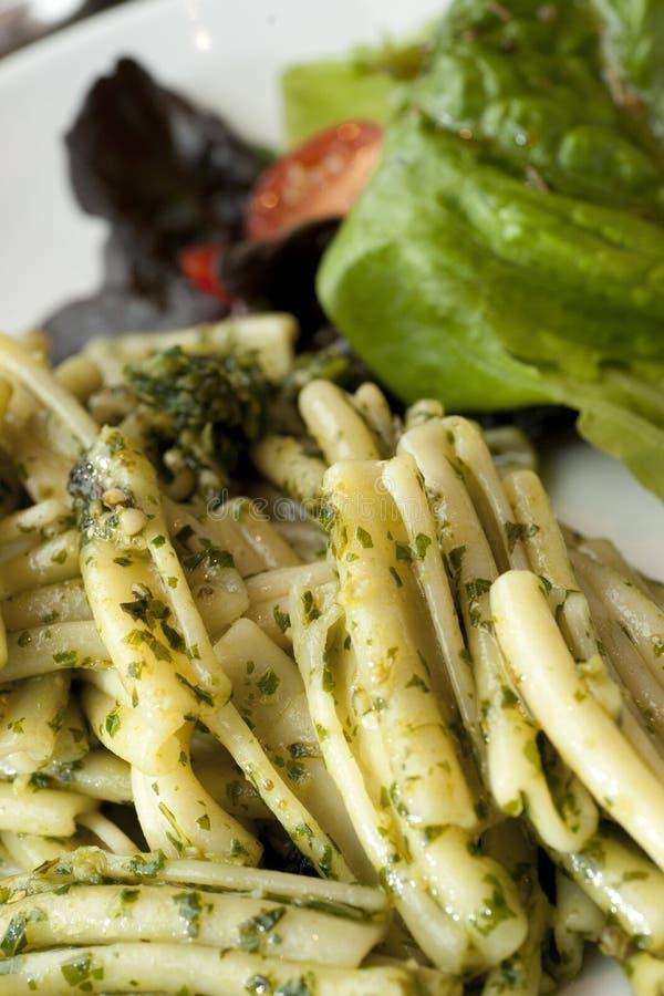 Plat de pâtes avec le pesto vert et salade d'un plat blanc photos stock